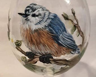 Hand painted wine glass of Nuthatch bird in tree with green leaves