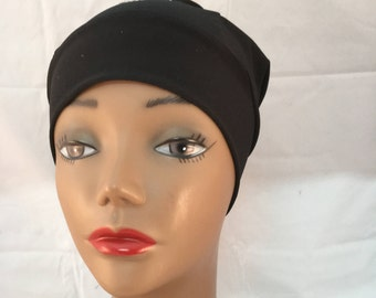 Black sluchy cap with baeast cancer ribbon in top of hat room for a scarf.