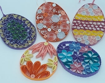 Quilled Easter Egg Ornaments. Choose from five colors/designs. Use as Rear View Mirror, Suncatcher or Package Hanger. Includes Gift Package.