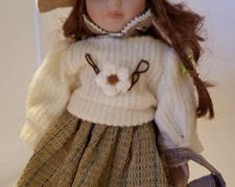 Porcelain doll auburn hair green eyes with winter outfit, porcelain doll with hat, porcelain doll wearing sweater 12 inches tall. DOLL