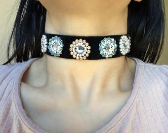 A black velvet choker with shiny clear ab, rose gold, silver, and white beads. with shiny centre gems.