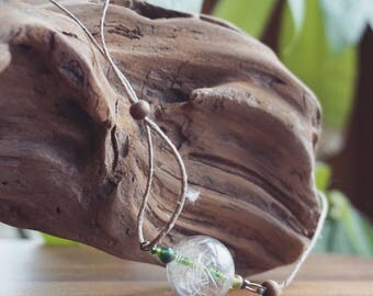 Glass ball with dandelion seed and green beads inside, on a hemp cord with wooden beads.