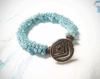 Beaded baby blue bracelet with military style button clasp