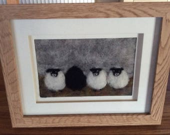 Needle felt 2d fibre art picture of a row of sheep made from sheeps wool in an oak frame.