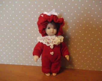 Little girl doll wearing red  romper/sleep suit with mop cap