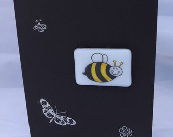 A glass magnet with a happy bee on a card: present in a card.