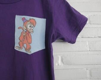 Purple Short Sleeve Pocket Tee Vintage Disney Aladdin Abu Size Medium