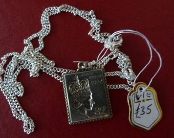 a solid silver postage stamp on silver chain