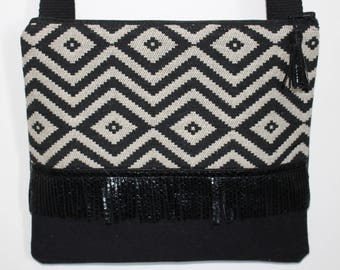 Black and beige graphic clutch bag with fringe