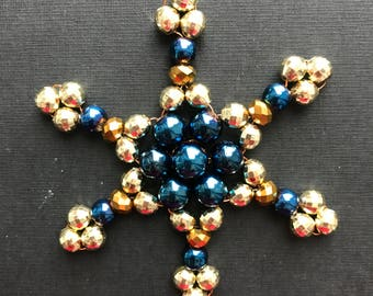 A six-pointed star for a Christmas tree. Ornament of their sparkling golden and blue beads. Winter festive decor.