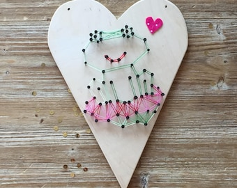 Heart shaped picture with frog in string art, creating in wood to hang on the wall