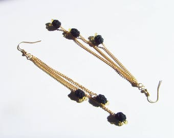 Long black and gold beads and gold chain earrings.