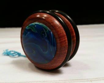 Exotic bloodwood wooden yo-yo with ocean mist side caps.