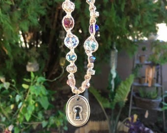Macrame hemp necklace with glass beads and metal lock pendant with rhinestones