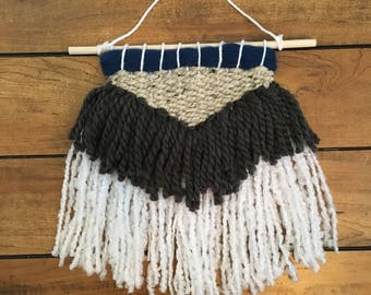 Navy blue, charcoal grey, oatmeal and white woven wall hanging