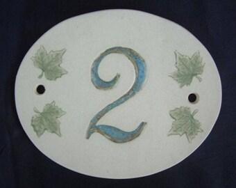 Oval door number, shape, number 2 blue on beige background, ivy leaves