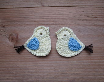 a couple of pale yellow, light blue and chocolate birds crochet