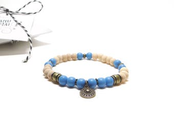 Bracelet of natural raw wood, blue wood beads and metal bronze with an ethnic charm