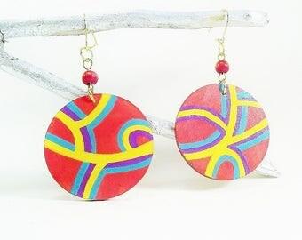 On earrings, dangle earrings colorful red background.