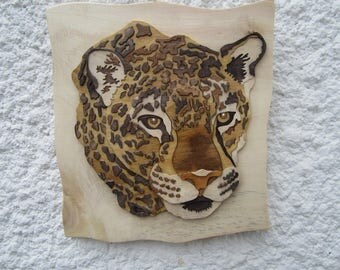 Inlay in relief of a jaguar head.