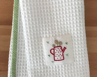 Handmade hand towel with Gerbera Daisies in watering can motif hand-embroidered by Apples N' Thyme