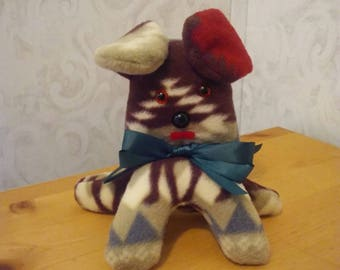 Puppy dog in fleece shades of brown. Hypoallergenic. Safety eyes n nose. Felt mouth. Satin ribbon at neckline. Measures 6 inches high.