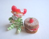 Tiny strawberry pixie figurine with faux victoria sponge cake