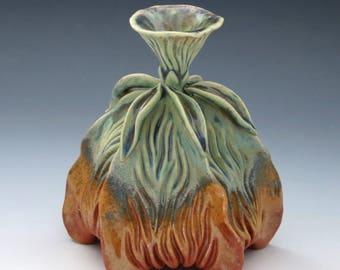 Carved porcelain vase in green, tan & orange, flower top