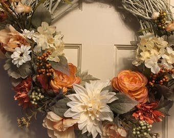 Fall grapevine wreath in a gentle, soft autumn pallet, on a glossy ivory wreath with dahlia, hydrangea, berries and more.