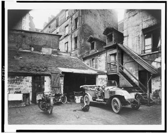 Automobile and two motorcycles in front of garage, Paris, France, 1930s