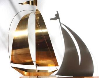 A sculptural, 1970s, brass sailboat, on an onyx base.