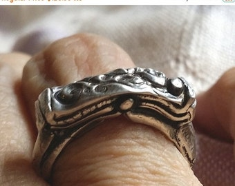 Hand modeled PMC design in silver 960 is mounted on an argentium silver band for a design that is both intricate and simple.  Size 8.25