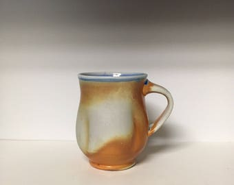 Hand thrown porcelain cup. Slipped on the outside with a glazed interior.  Fired in a reduction soda kiln.