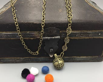 Diffuser necklace. Antiqued brass sphere locket with chain and refill poms.