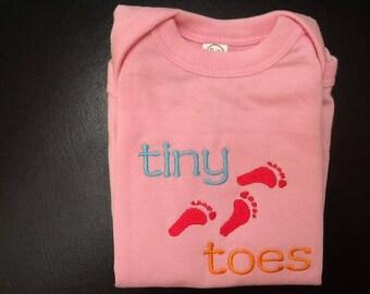 Tiny toes on baby onesie