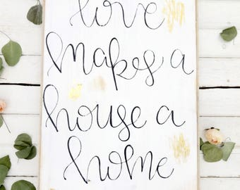 love makes a house a home with gold leaf  black and white rustic wood sign