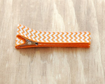 Girls , baby , toddler barrette fully lined on a double prong alligator clip in orange grosgrain ribbon with white chevron zig zag stripes