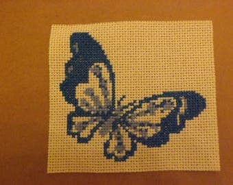 Blue butterfly embroidered on unbleached canvas