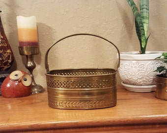 Vintage brass basket with handles and cut out detail.