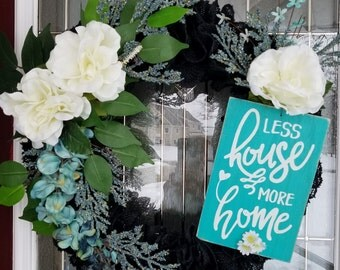 """16"""" black burlap wreath with teal, white, flowers. Sign reading """"less house more home"""""""