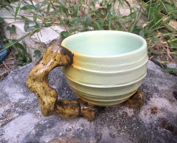 porcelain mug in pale green and golden orange with stone handle