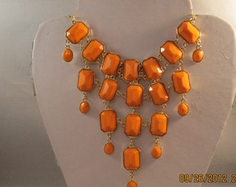 4 Row Bib Necklace with Golg and Pale Orange Pendantd on a Gold Tone Chain