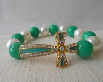 Green and White Sea Shell Pearl Stretch Bracelet with a Gold, Green and Clear Rhinestone Cross