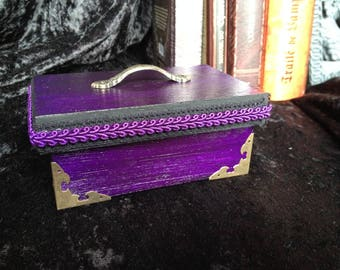 Wooden box painted purple with handle and brass corners