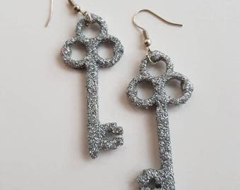 Sparkly silver key earrings made from wood and covered in glitter.