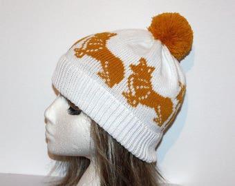 White pompom beanie hat with golden Corgi dogs