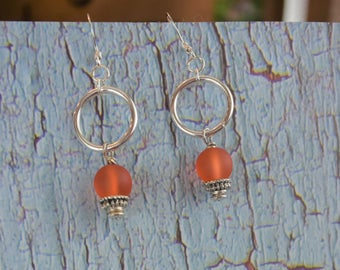 Silver loops with orange ball