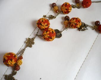 Necklace composed of wool felt and embroidered in color rust, yellow and black