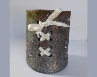 Small pencil retuning bronze green Raku adorned with a white satin ribbon holder