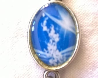 Silver cabochon flowers climb up on a gorgeous blue background